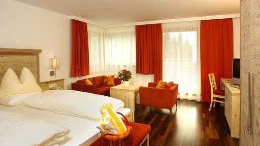 Exklusives, großzügiges 2-Raum-Appartement mit dunklem Holzfußboden, gemütlicher Sitzecke und King-Size-Betten.